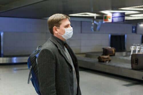 Мъж с маска, чака на летището багажа си