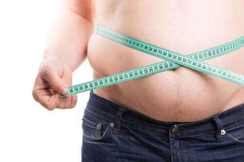 Отървете се от коремните мазнини: мъж си измерва талията