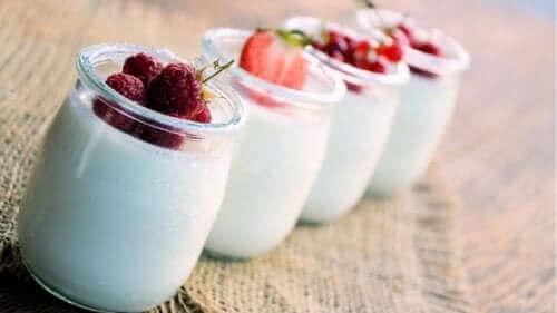 Снимка на четири стъклени бурканчета с кисело мляко и отгоре с различни плодове малини, ягоди и т.н.