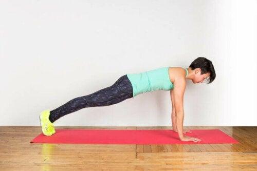 Една млада жена прави планк упражнения