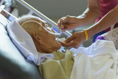 Най-уязвимите групи към COVID-19: на болен възрастен мъж му мерят температурата