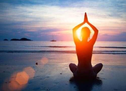Добро психично здраве: снимка на жена, която прави йога на брега на морето