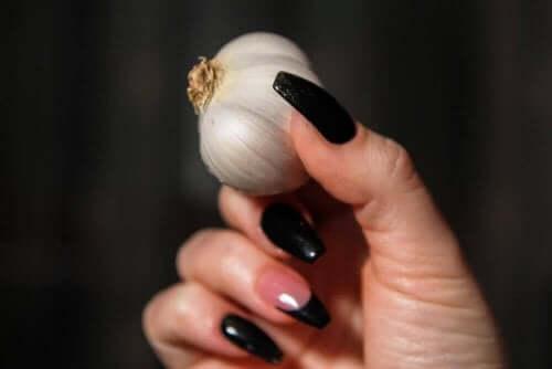 Една женска ръка държи чесън