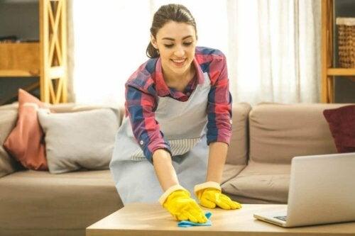 Почистване и дезинфектиране на дома: млада жена с ръкавици почиства пода