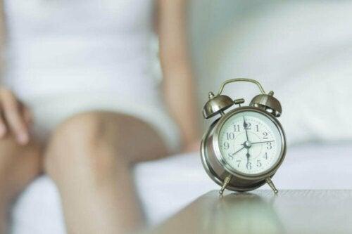 Семейното разбирателство: часовник будилник и жена на заден план