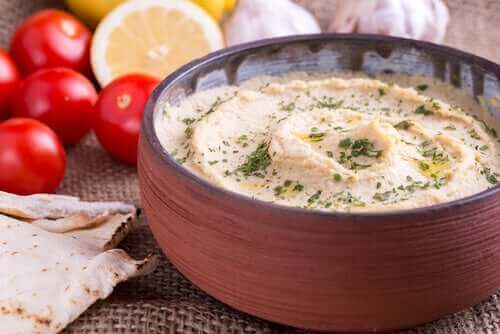Хумус с червен пипер: хумус в глинена купа и около нея червен домат и лимон.
