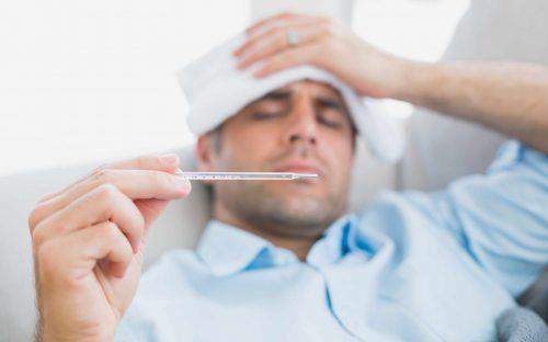 Коронавирусът засяга повече мъжете: мъж с температура и държи в ръка термометър.