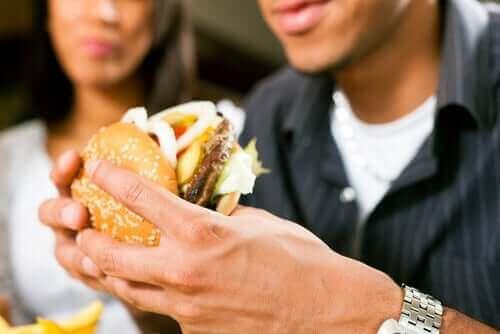 Грешки при хранене: мъж яде хамбургер