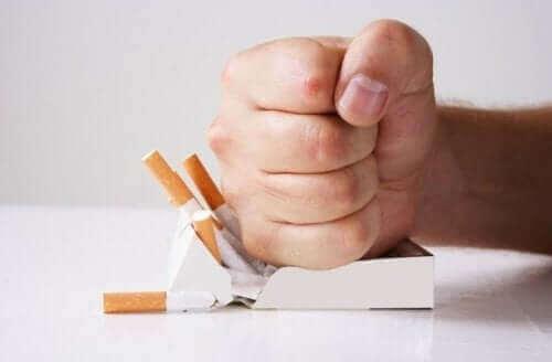 Една свита в юмрук ръка смачква кутия цигари