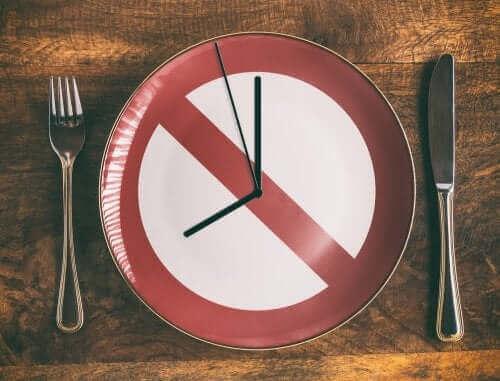 """Пътнически знак """"Стоп"""" направен като часовник и вилица и нож до чинията."""