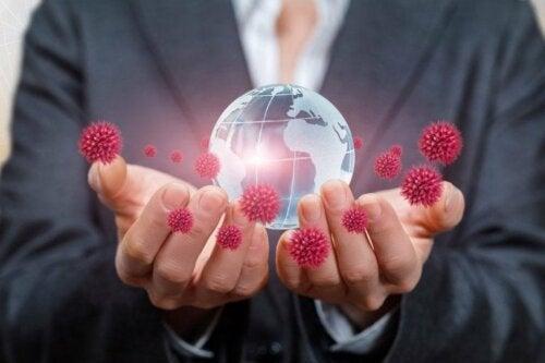 Пандемията от коронавирус: две ръце държат макет на земното кълбо и коронавируси