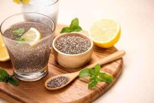 Семена от чия в дървена купичка, половин лимон и напитка с чия в стъклена чаша