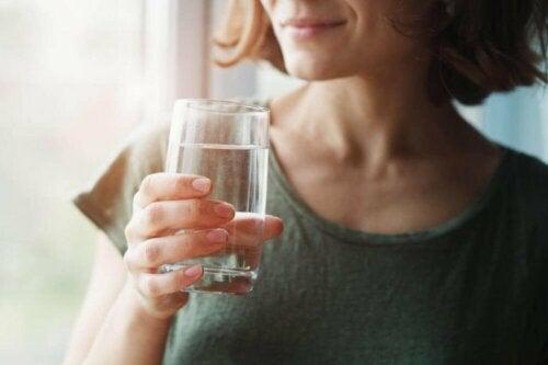Измислици за коронавируса: жена държи чаша вода