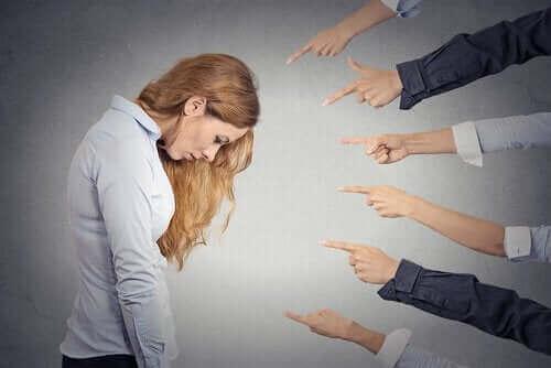 Жена с наведена глава и около нея 6 мъжки ръце я сочат с пръст