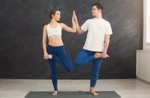 Една двойка мъж и жена стоят на един крак