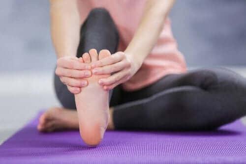 Една млада жена си прави масаж на краката