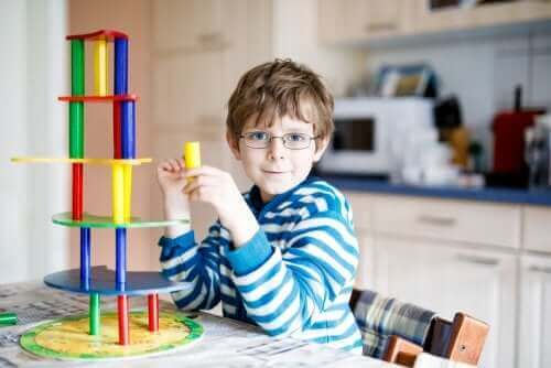 Проблеми със зрението при децата: момче с очила си играе на една маса