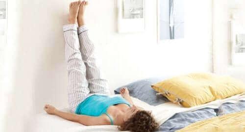 Подути глезени и крака: една жена с вдигнати крака на стената