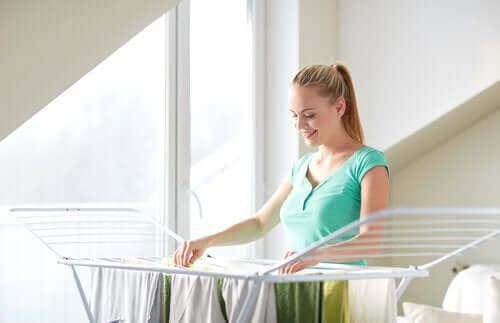 Жена простира дрехи навън