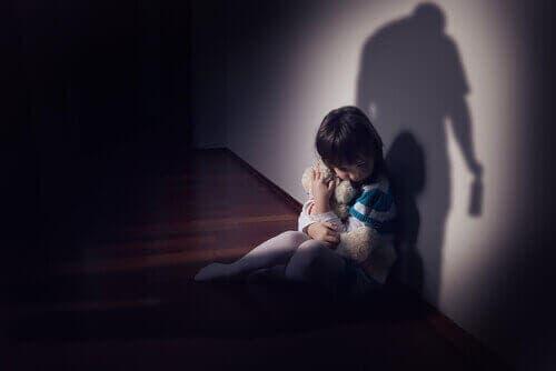 Уплашено дете седи до една стена
