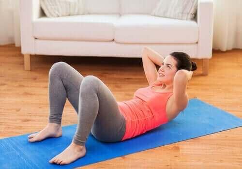 Упражнения за корема: една млада жена прави коремни преси