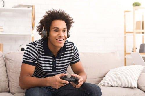Едно момче се усмихва и играе на видео игра