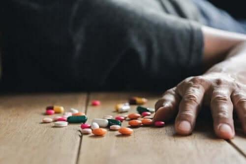 Натравяне с лекарства: човек лежи до лекарства на пода