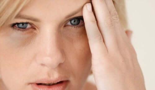 Снимка на лице на жена, която има главоболие