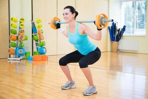 Една млада жена прави клякания с тежести