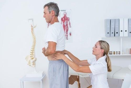Лекар преглежда гърба на пациент