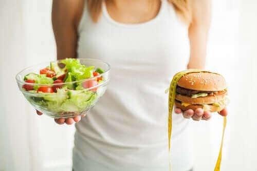Предотвратяване на затлъстяването: една жена държи салата и хамбургер