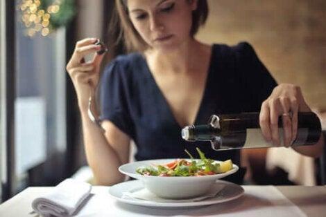 Пропускането на вечерята: една жена слага зехтин на салата