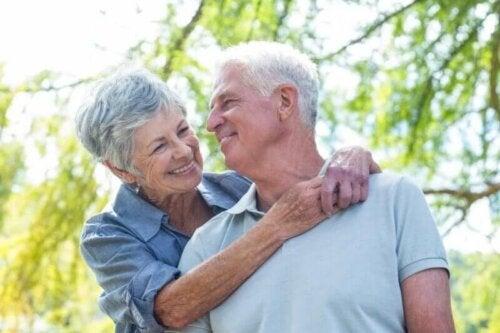Възрастни мъж и жена прегърнати и се усмихват